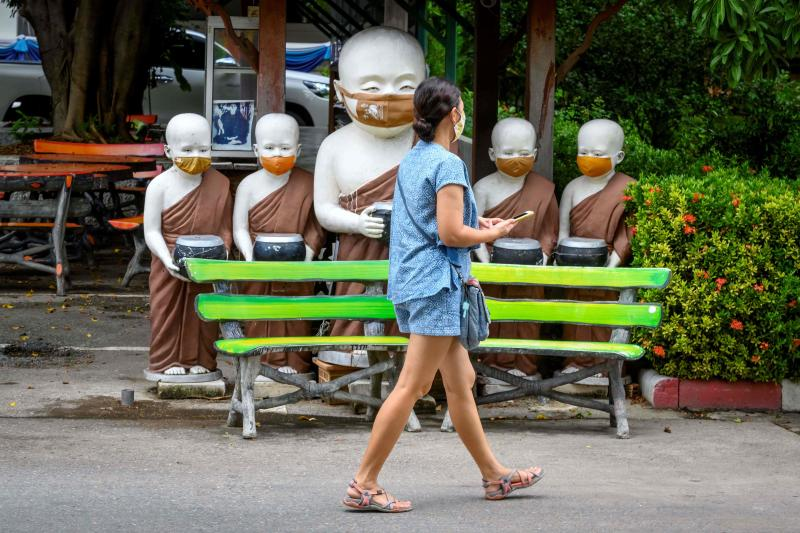 A visitor wearing a protective face mask walks in front of statues of Buddhist monks, faces covered with masks, in Wat Chedi Luang Buddhist temple in Chiang Mai on Saturday. (AFP photo)