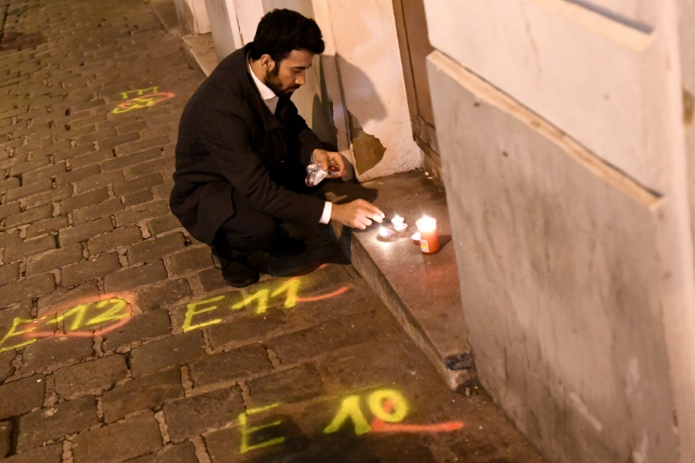 A man lights candles near the scene of the deadly shooting in Vienna.