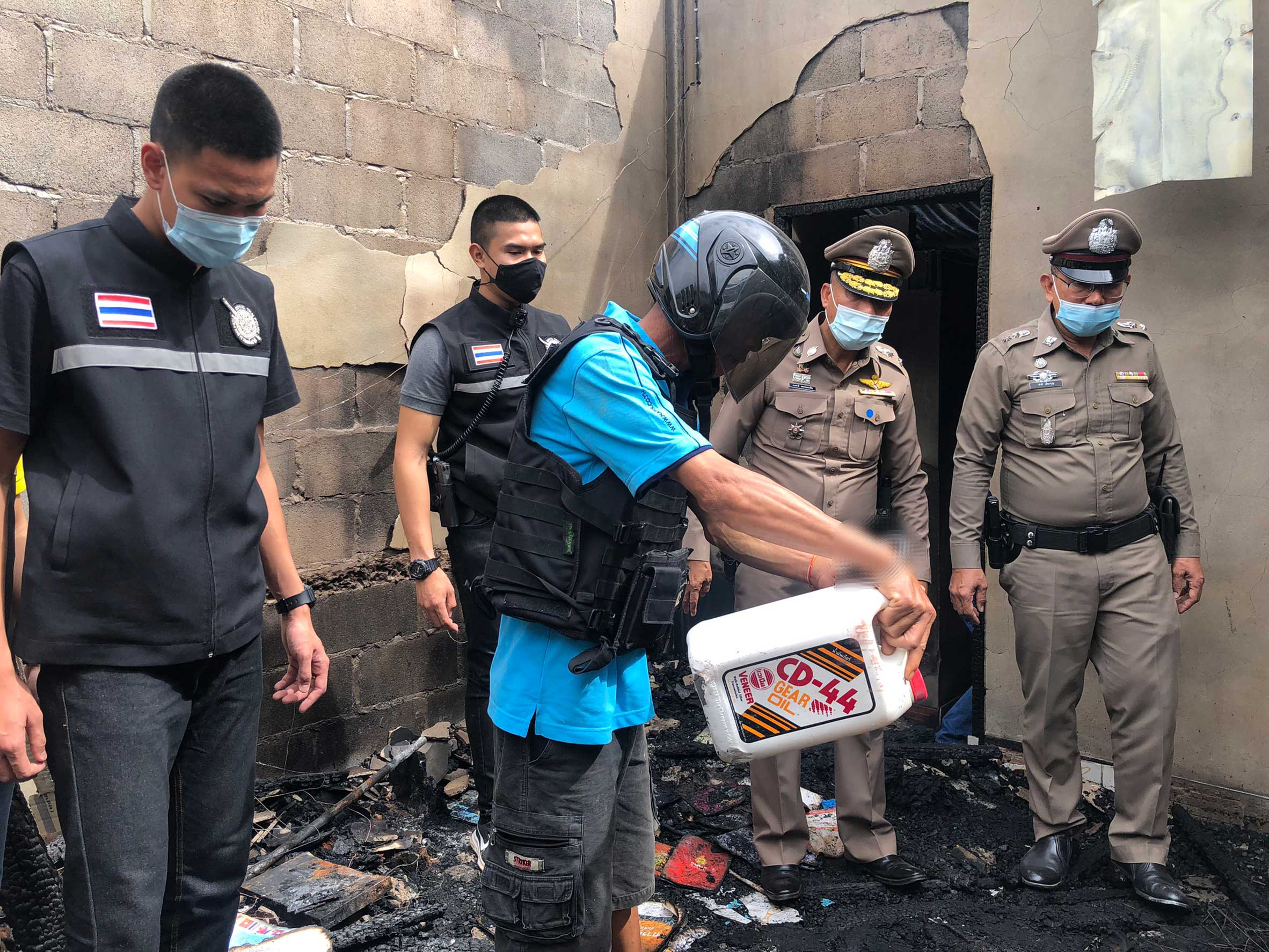 Phan Thopa, 50, during the crime re-enactment at his burned house in Nakhon Phanom on Friday. The man admitted using a hammer to beat his wife and their teenage son senseless, and setting fire to them. (Photo: Pattanapong Sripiachai)