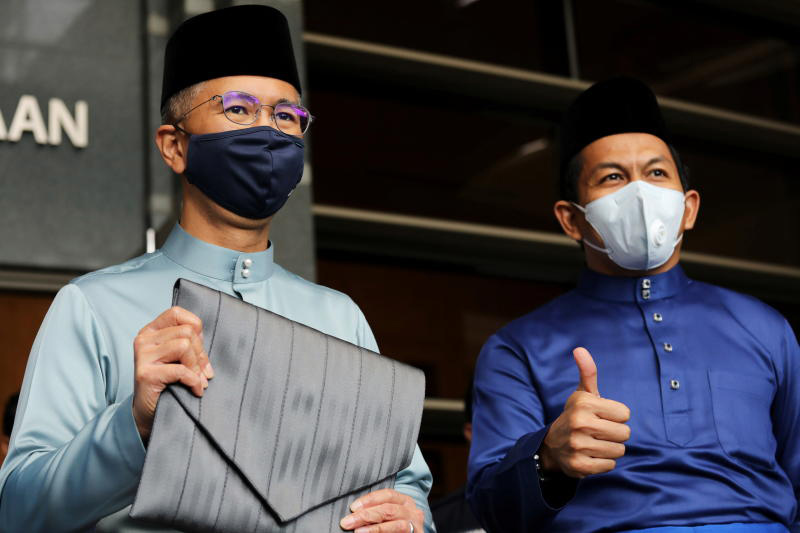 Malaysian Finance Minister Tengku Zafrul Abdul Aziz holds a bag containing the 2021 budget as he poses for a picture outside the Finance Ministry building in Putrajaya on Friday.(Reuters photo)