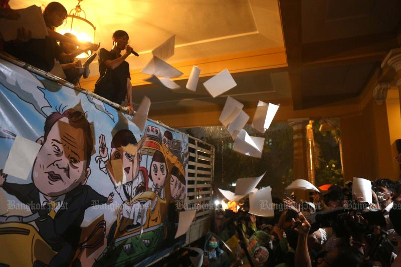 """Student activists throw 10,000 copies of a """"resignation form"""" intended for Education Minister Nataphol Teepsuwan from a lorry into the ministry grounds during a rally on Oct 2, 2020. (Photo by Pattarapong Chatpattarasill)"""