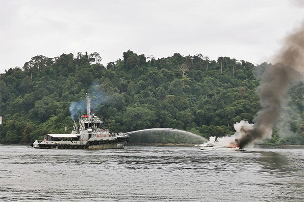 HTMS Panyi douses a fire on speed boat Fiona off mainland Phangnga on Sunday. (Photo by Achadtaya Chuenniran)