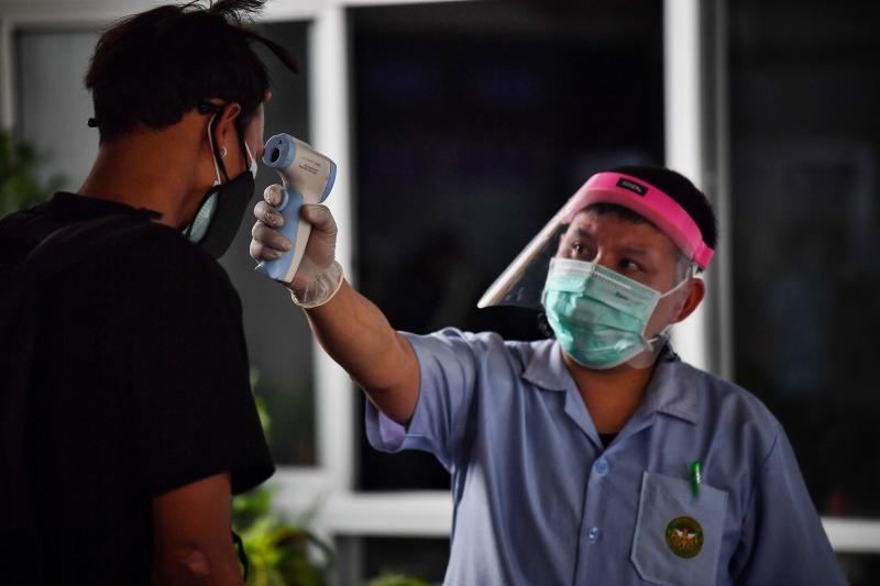 FILE PHOTO: A man has his temperature taken as a preventive measure against the spread of the Covid-19 novel coronavirus at the Ministry of Transport at the border crossing over the second Thai-Myanmar Friendship Bridge in Mae Sot in Tak province, Oct 29, 2020. (AFP)