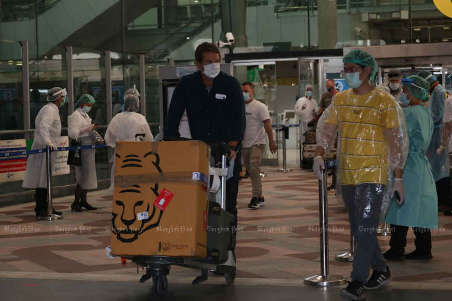 Disease control officials guide arrivals at Suvarnabhumi airport to a quarantine process last month. (Photo by Varuth Hirunyatheb)
