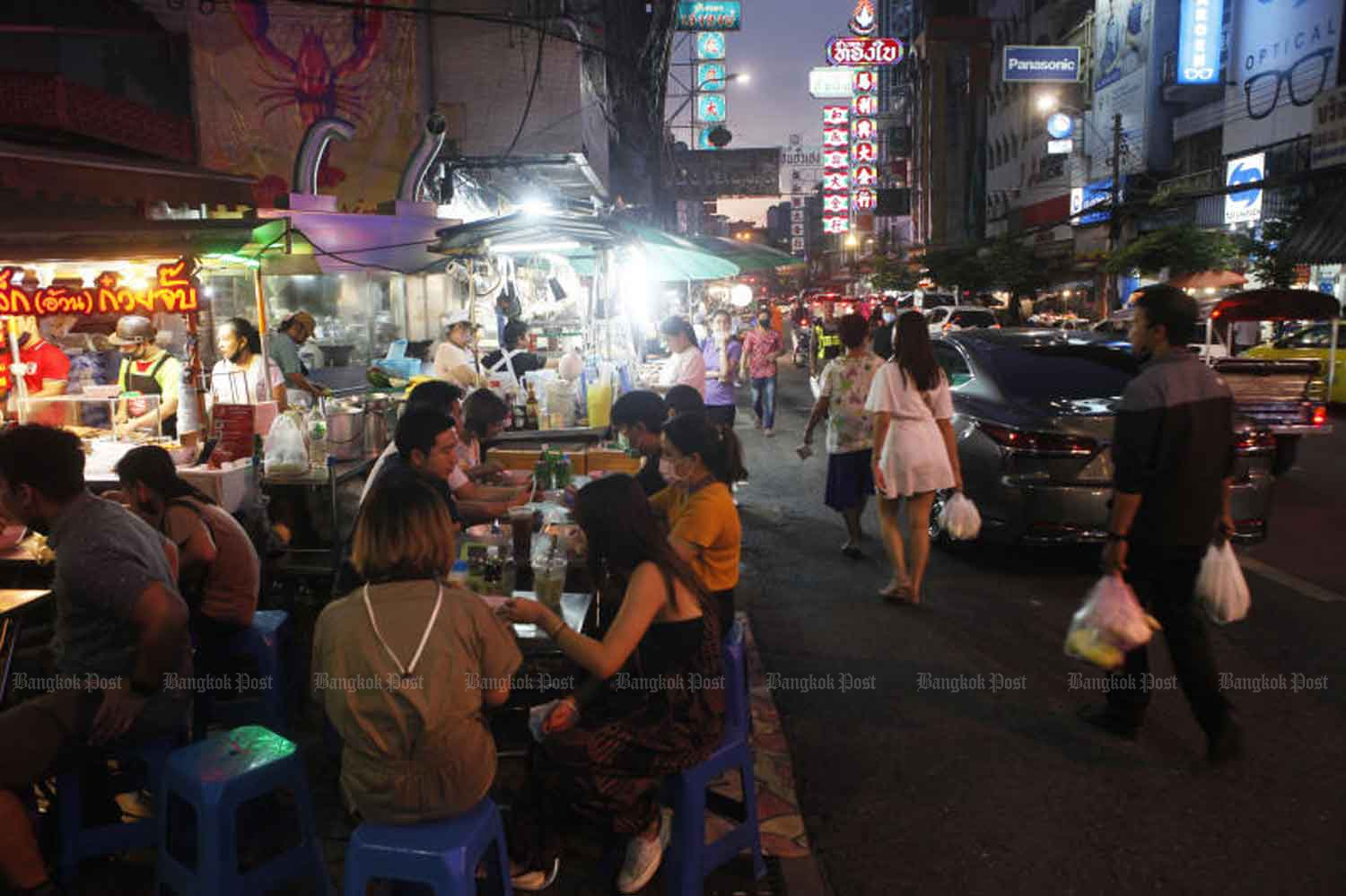 People sit down to eat at food stalls along Yaowarat Road, one of Bangkok's main street food attractions, last month. (Photo by Nutthawat Wicheanbut)