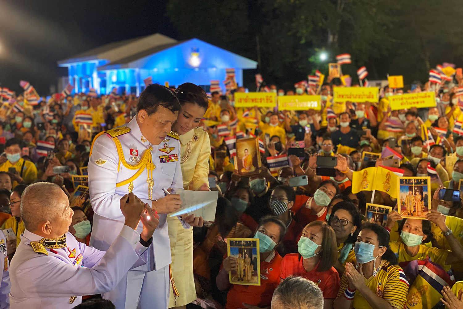 Written with love: His Majesty the King, accompanied by Her Majesty the Queen, writes a message for a well-wisher at Wing 23 in Udon Thani before presiding over the opening of an office building at Udon Thani Juvenile and Family Court in Muang district.