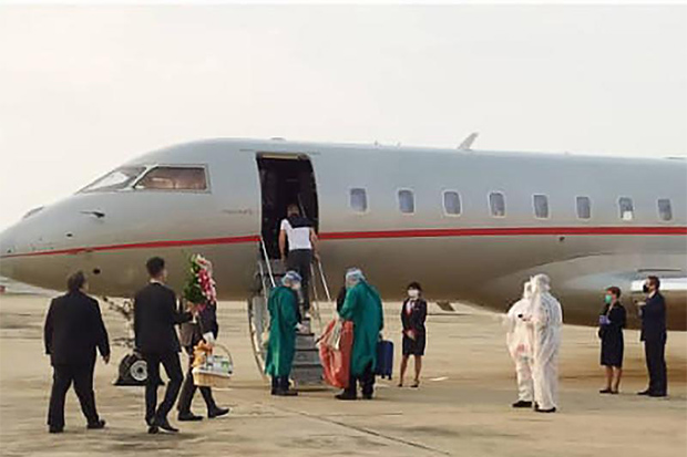 Health officials in protective gear escort Hungary's Foreign Minister Peter Szijjarto aboard his plane as he leaves Bangkok for Budapest on Nov 4 after testing positive for the Covid-19 virus in Thailand. (Photo: Public Health Ministry/AFP)