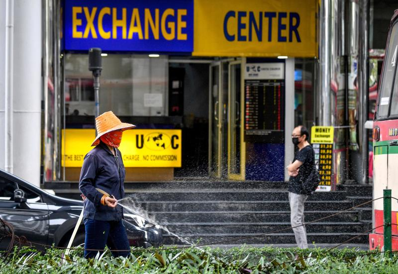 A municipal worker waters plants outside a currency exchange office in Bangkok on Sept 23, 2020. (AFP file photo)