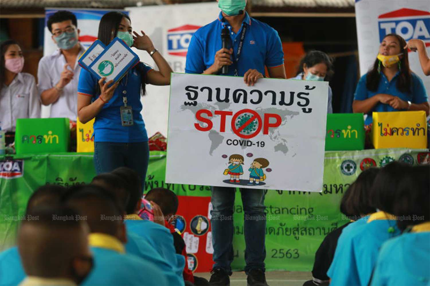 Officials educate students at Bang Sao Thong School in Samut Prakan province about Covid-19 and how to protect themselves on Thursday morning. (Photo by Somchai Poomlard)