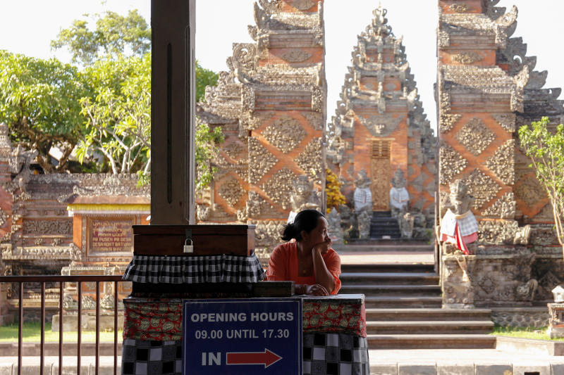 A woman ticket vendor waits for tourists at the entrance to Puseh Temple at Batuan Village in Gianyar, Bali, Indonesia. (Photo: Reuters)