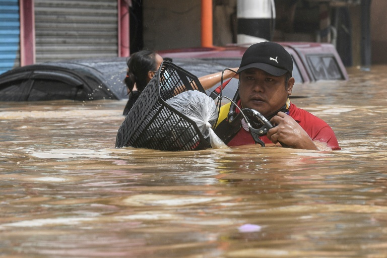 The flood water in some Manila streets was up to shoulder height. (Photo: AFP)