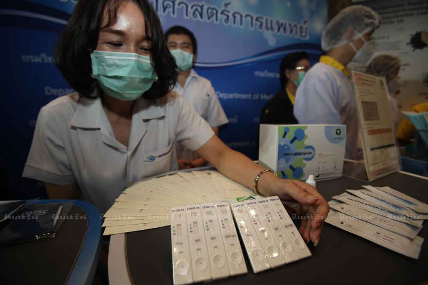 A public health official shows Covid-19 test kits developed by the Public Health Ministry. They are among items on display at the exhibition 'Smart Living with Covid-19' hosted by the ministry at Pullman King Power Hotel, Bangkok and at the heart of plans to gradually reopen the country. (Photo by Nutthawat Wicheanbut)