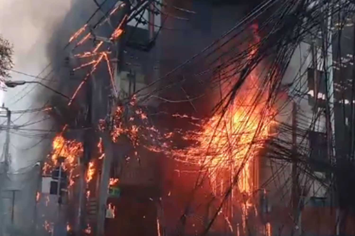 Overhead cables are ablaze in front of Sawasdee Wittaya School on Sukhumvit Soi 31 on Saturday afternoon, apparently the result of an electrical short-circuit. (Captured from clip via @js100radio Twitter)