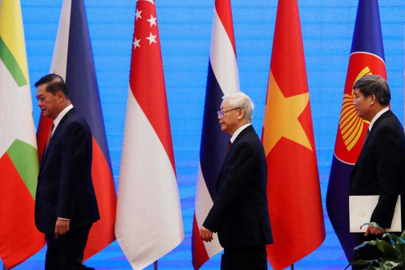 Vietnam's Communist Party General Secretary and President Nguyen Phu Trong (centre) walks past flags of the Asean member countries before opening the 37th Asean in Hanoi on Thursday. It was followed by other related meetings, including the East Asia Summit on Saturday. (Reuters photo)
