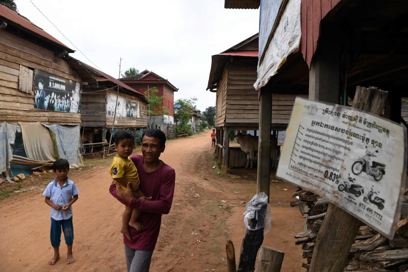 A man carrying his son walks past flyers of microfinance services displayed outside a house at a village in Siem Reap province, Oct 15, 202. (AFP photo)