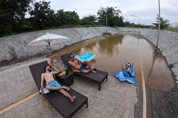Jitiwat Nakchamsilp (left) lies on a lounge chair with a man and a girl in a flooded underpass in Non Sung district of Nakhon Ratchasima. (Photo from Jetiya Nakchamsilp Facebook account)