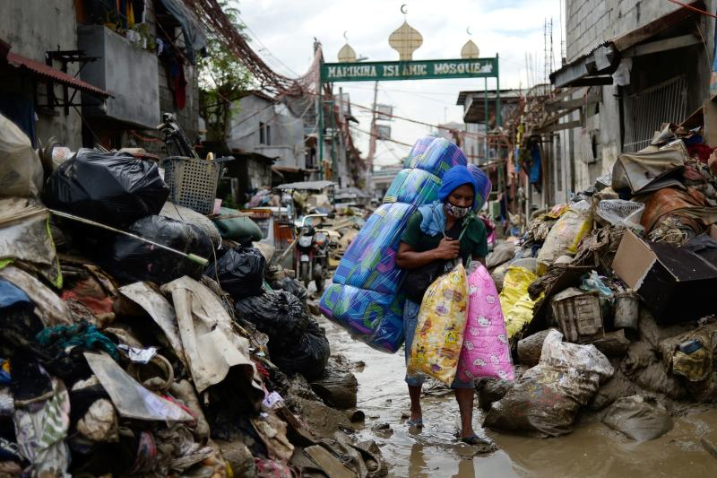 A man selling pillows and mattresses walks past debris from the flood brought by Typhoon Vamco, in Marikina, Metro Manila, Philippines on Monday. (Reuters photo)