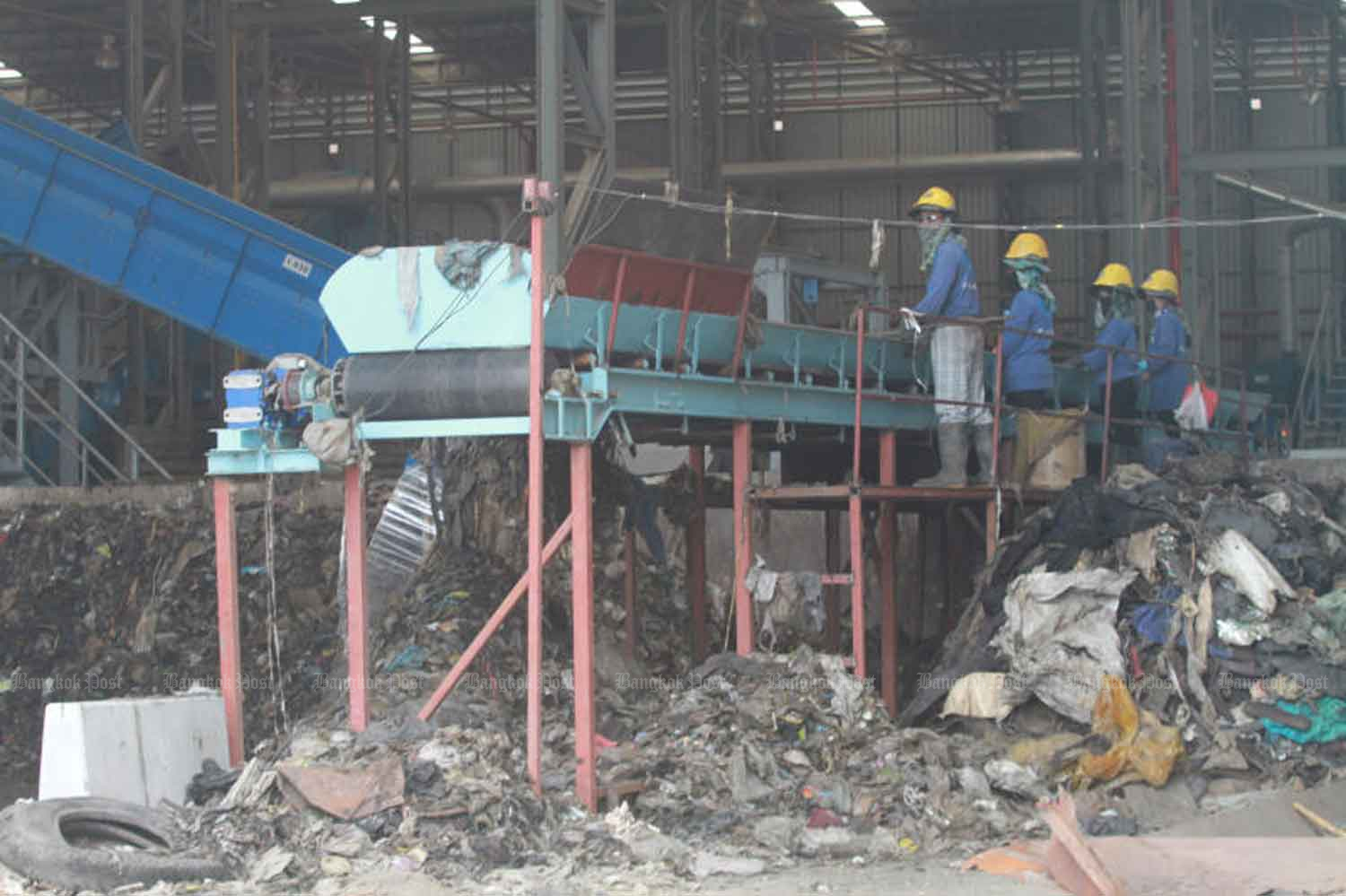 Workers feed garbage onto a conveyor belt at a biomass power plant in Samut Prakan province. (Bangkok Post file photo)