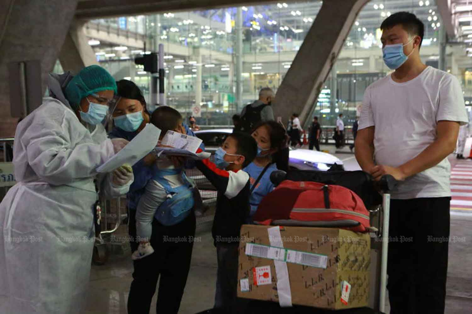 A disease control official receives a Chinese family who arrives at Suvarnabhumi airport in Samut Prakan province last month with special tourist visas. (Photo by Somchai Poomlard)