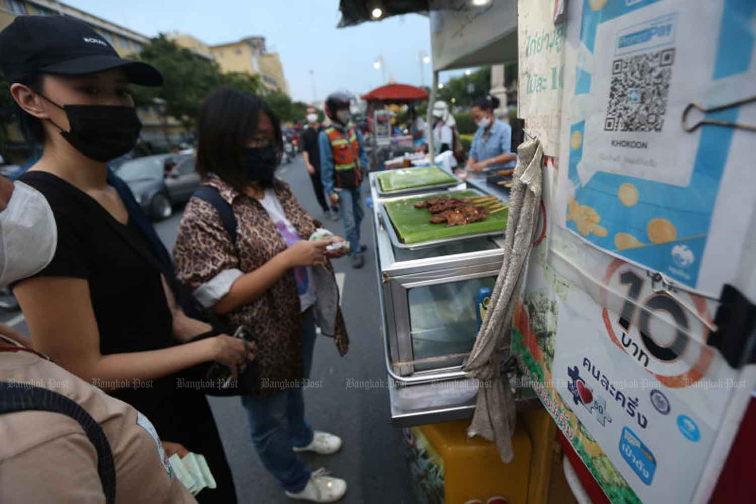 Consumers are at the stall of a food vendor who participates in the government's co-payment scheme aimed at economic stimulation, in Bangkok this month. (Photo by Varuth Hirunyatheb)