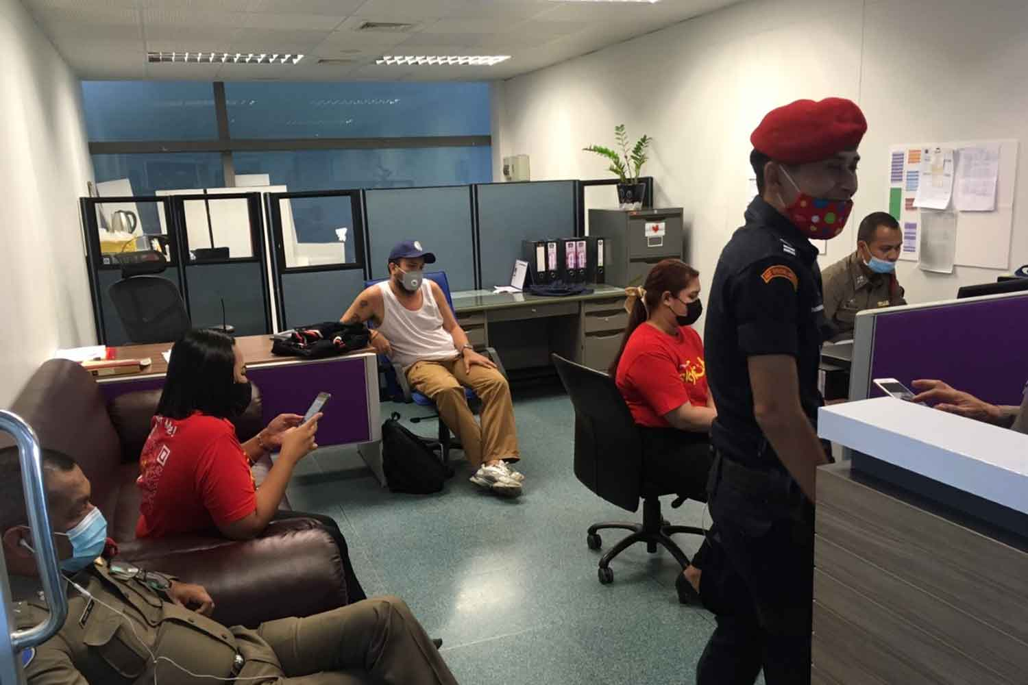Mike Wims, seated centre, in the Phuket airport security office for questioning by police. (Photo: Achadtaya Chuenniran)