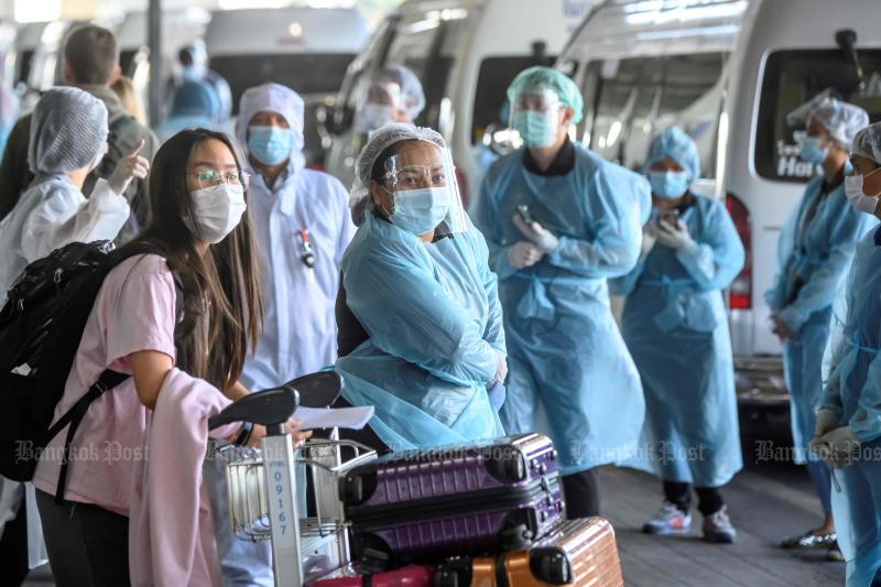An employee wearing personal protective equipment (PPE) talks to an arriving international flight passenger about her hotel transfer for the compulsory 14-day Alternative State Quarantine (ASQ), to prevent the spread of the Covid-19 coronavirus, at Suvarnabhumi Airport in Bangkok on Monday. (AFP photo)