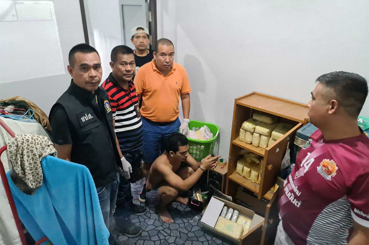 Police pose with some of the drugs seized at a house in Hat Yai district, Songkhla province, on Nov 14. Suspected drug dealer Sompong Mugem (squatting) was arrested. (Photo: Assawin Pakkawan)