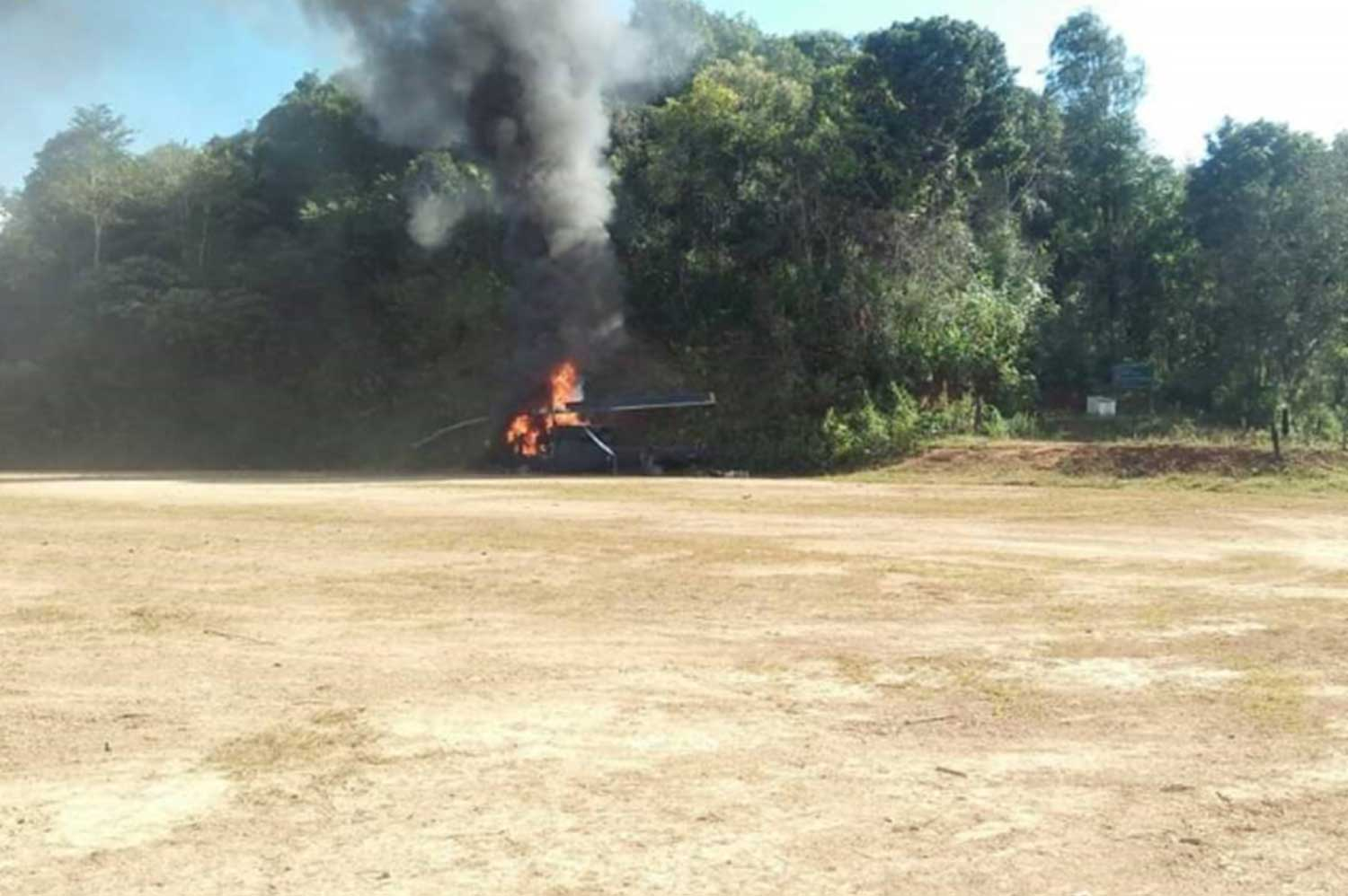 Smoke pours from the burning helicopter after it made an emergency landing in a school field in Mae Chaem district, Chiang Mai province, after developing engine trouble on Tuesday afternoon. The 11 people on board, including Chiang Mai deputy governor Samroeng Chaisen, escaped unhurt. (Photo: Phamumet Tanraksa)