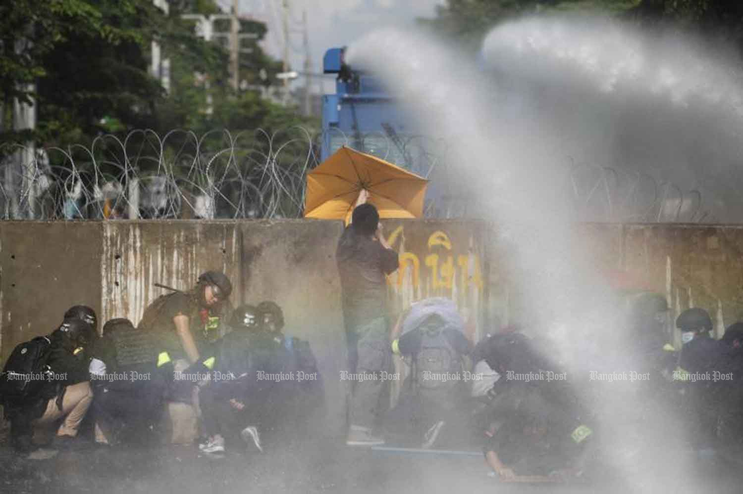 Demonstrators in protective gear take cover behind concrete barriers as riot police shoot water cannon to deter them from breaking through a barricade erected to block access to the parliament building, on Tuesday, in Dusit district of Bangkok. (Photo by Wichan Charoenkiatpakul)