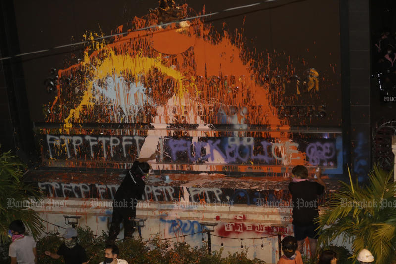 A protestor paints a plaque of the Royal Thai Police during a rally on Wednesday. (Photo by Pornprom Satrabhaya)
