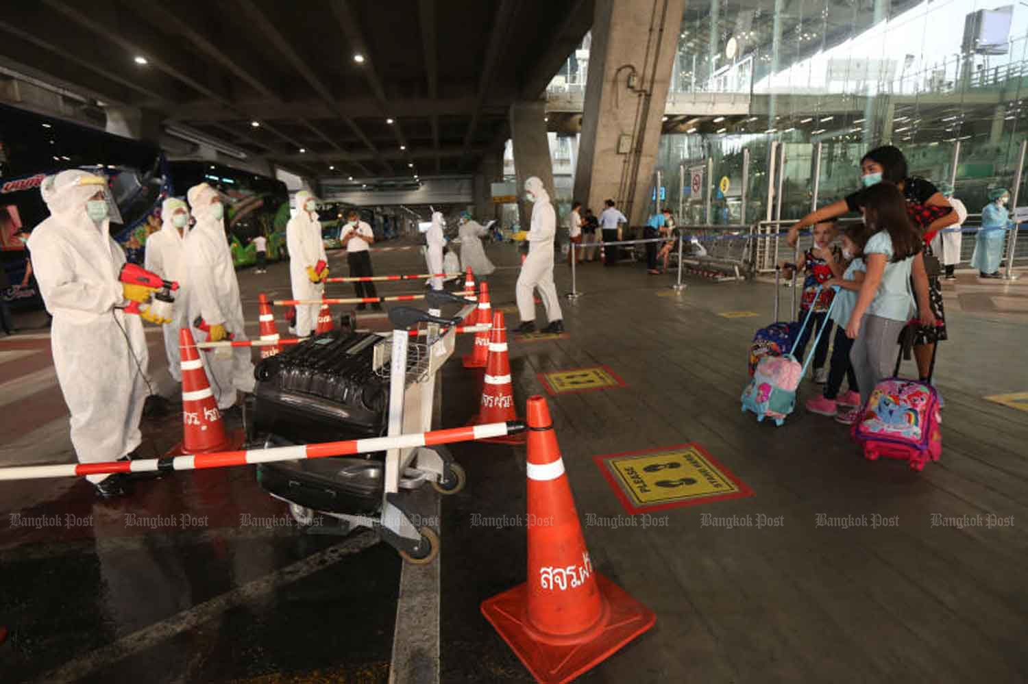 A family arrives at Suvarnabhumi airport in Samut Prakan province and heads for quarantine. (Photo: Varuth Hirunyatheb)