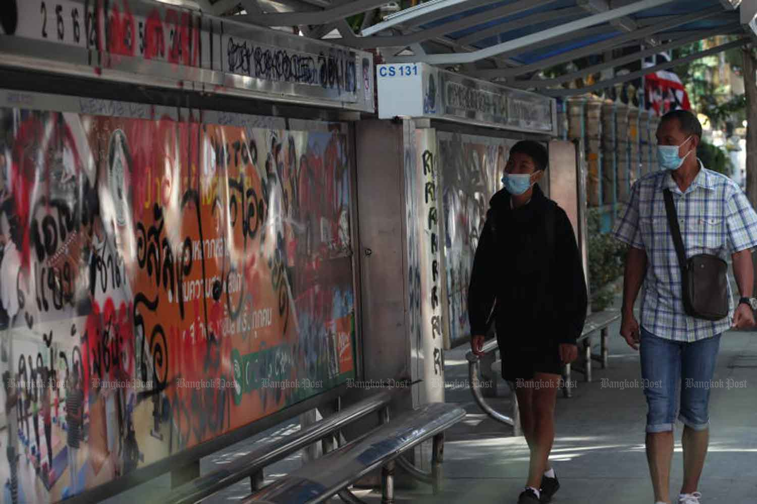 Pedestrians walk past a paint-sprayed bus stop in front of the Royal Thai Police Office in Pathumwan district, Bangkok, on Thursday, following the anti-government protest there and at adjacent Ratchaprasong intersection on Wednesday night. (Photo: Apichit Jinakul)