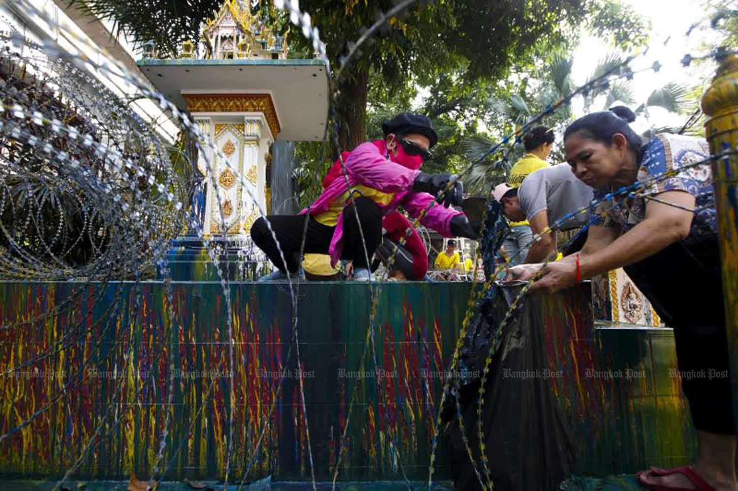 Volunteers clean the shrine at the gate to Royal Thai Police Headquarters in Pathumwan district, Bangkok, on Friday. (Photo: Pattarapong Chatpattarasill)