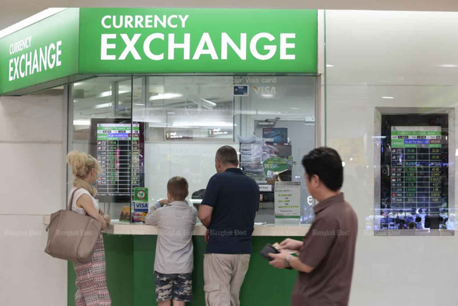 Foreigners make use of a currency exchange booth in Bangkok. The Bank of Thailand on Friday announced new measures to curb the baht's appreciation. (Bangkok Post file photo)