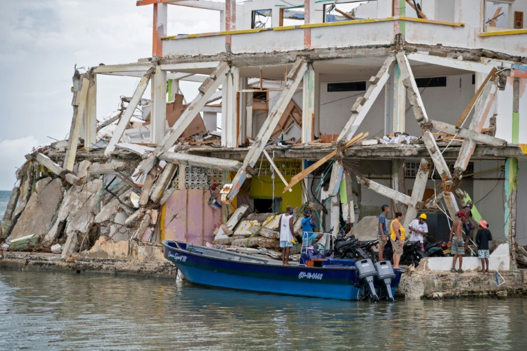 People inspect a damaged building after the passage of Hurricane Iota in Providencia, Colombia