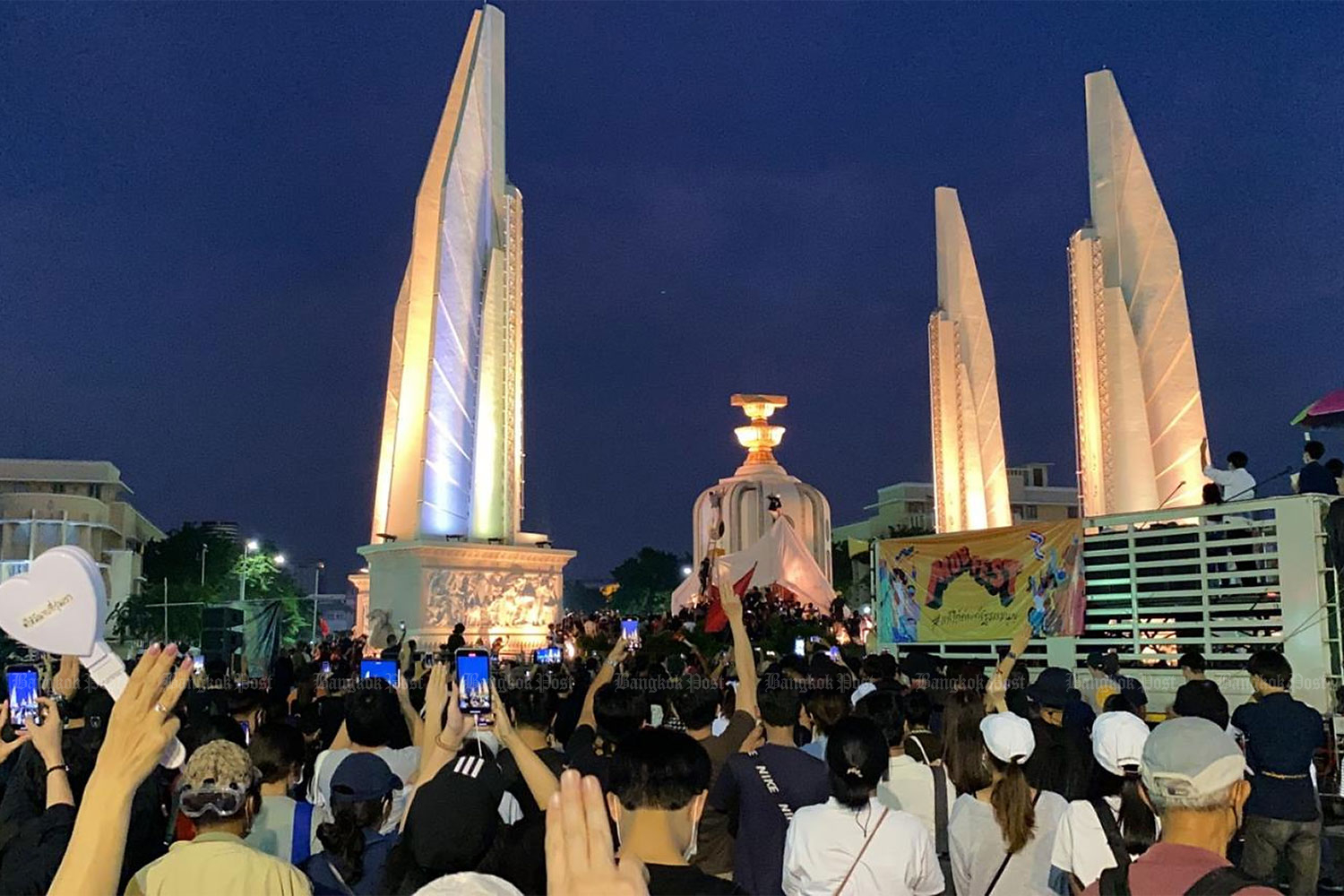 Pro-democracy protesters hold up at the three-finger salute at Democracy Monument during an anti-government rally in Bangkok earlier this month. (Photo by Nutthawat Wichieanbut)