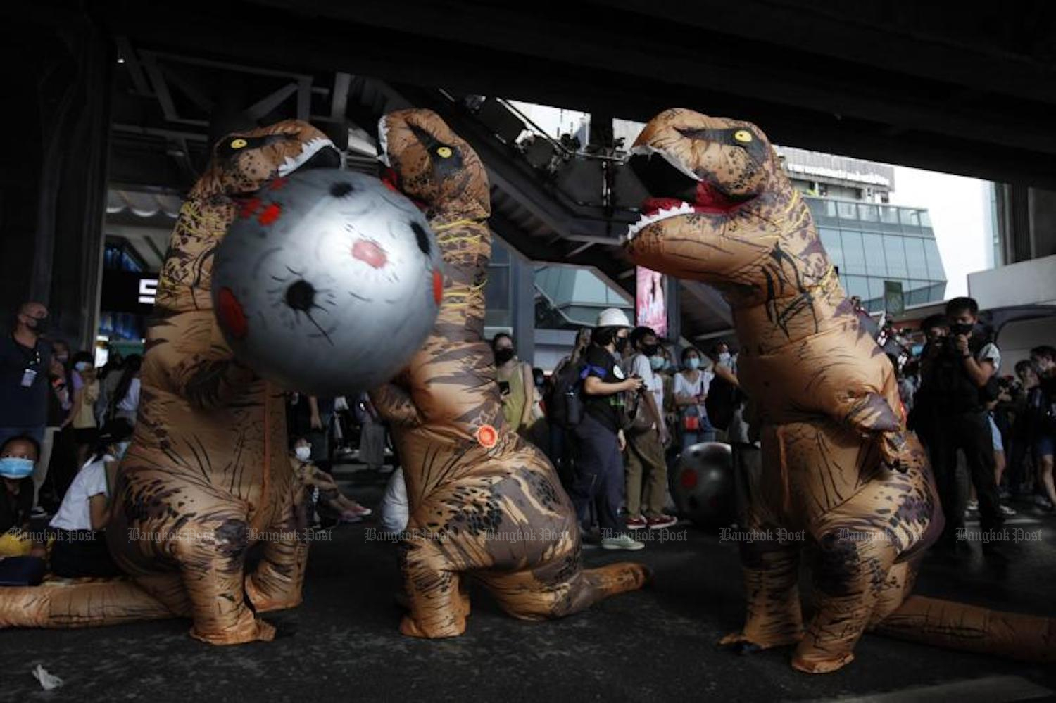 Protesters wearing dinosaur costumes try to flee from an approaching inflatable asteroid at the Bad Student rally at the Siam BTS station on Saturday. (Photo: Wichan Charoenkiatpakul)