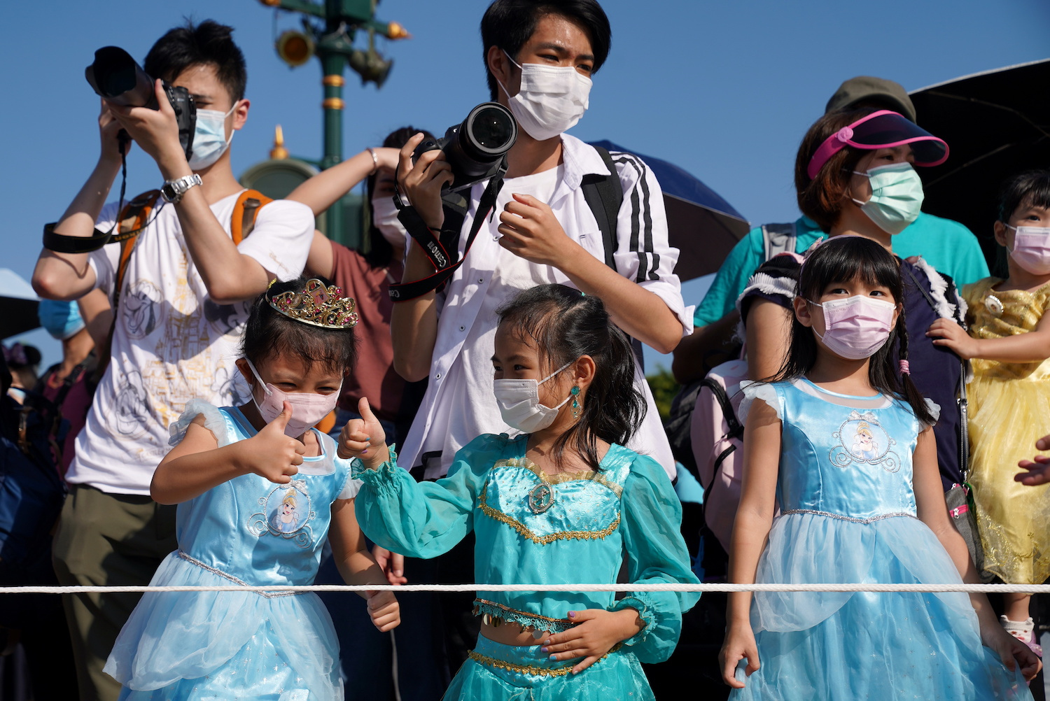 Children and adults wearing face masks enjoy an outing at Hong Kong Disneyland Resort on Friday. (Reuters Photo)