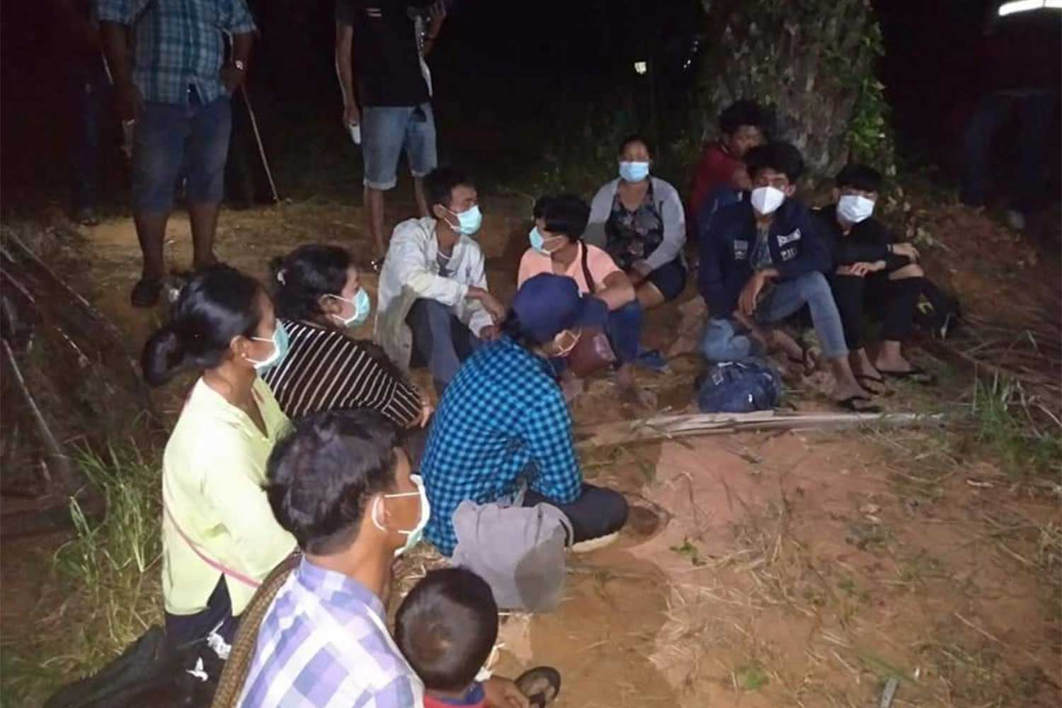 Twelve migrants from Myanmar are detained at the rubber plantation where they were caught after sneaking over the border in Muang district of Prachuap Khiri Khan early Saturday. (Supplied photo via Chaiyot Satyaem)