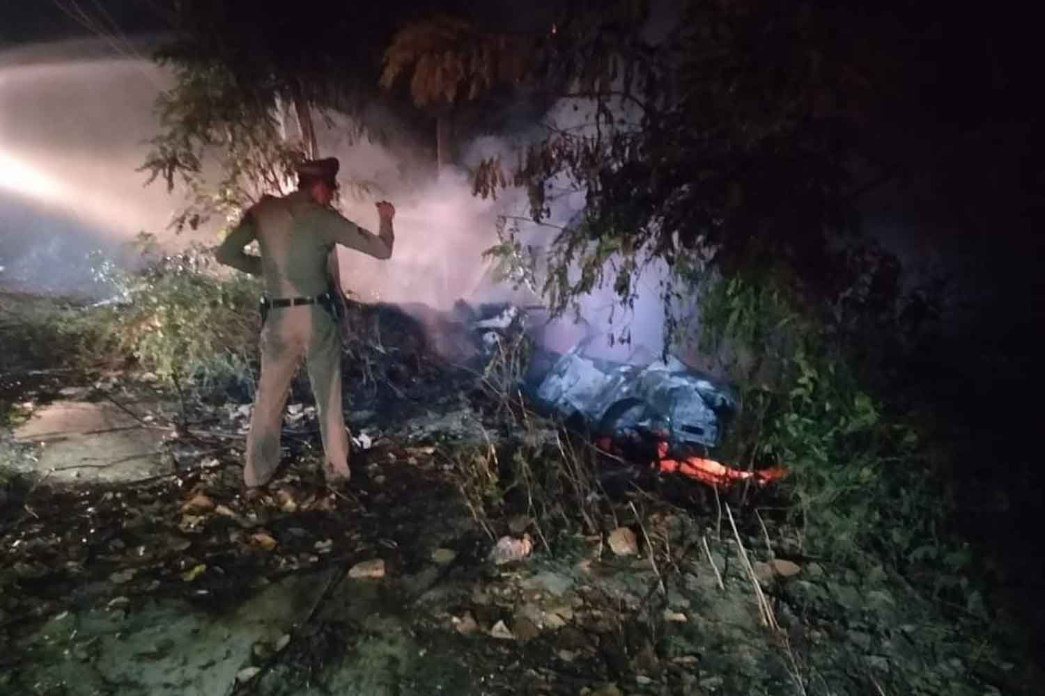 A police officer examines the car that skidded off a road in Ban Lat district, Phetchaburi province, and went up in flames early Sunday. Two men were killed and one injured in the accident. (Photo by Chaiwat Satyaem)