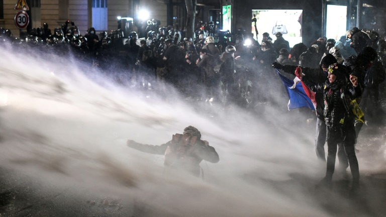 Police in Paris spray water cannon at protesters opposed to a French draft law seeking to limit the filming of police officers on duty.
