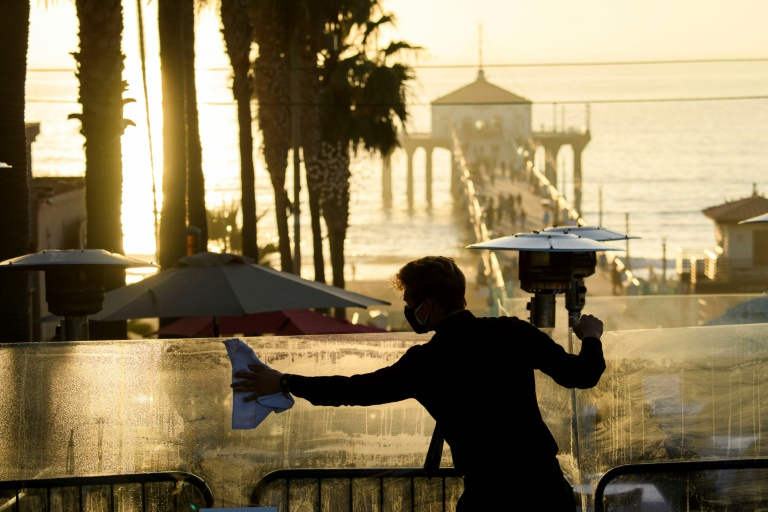 A restaurant employee cleans a plexiglass table divider while preparing for outdoor dining service in Manhattan Beach, California, a few hours before the start of the new 10pm to 5am curfew.