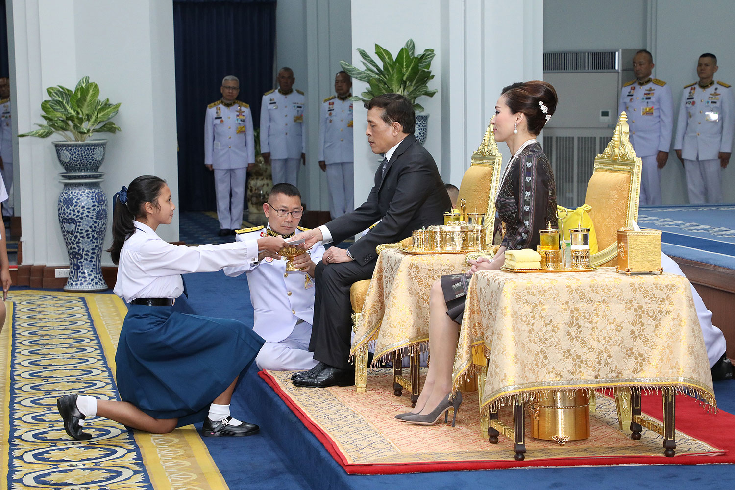 Incentive to learn: His Majesty the King hands a scholarship under His Royal Highness Crown Prince Maha Vajiralongkorn's Scholarship Foundation to a student at Chitralada Palace. His Majesty is accompanied by Her Majesty the Queen. (Photo: Royal Household Bureau)