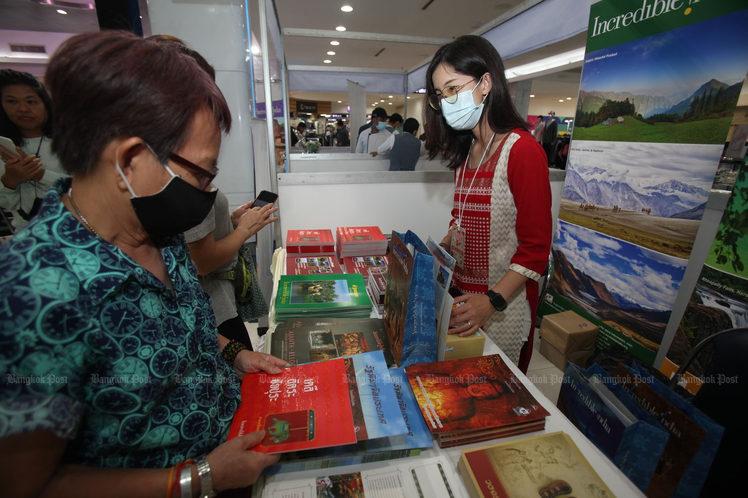 People wearing protective masks visit a booth at the Bay of Bengal cultural exhibition at MBK Center in Bangkok on Friday. (Photo by Nutthawat Wichieanbut)