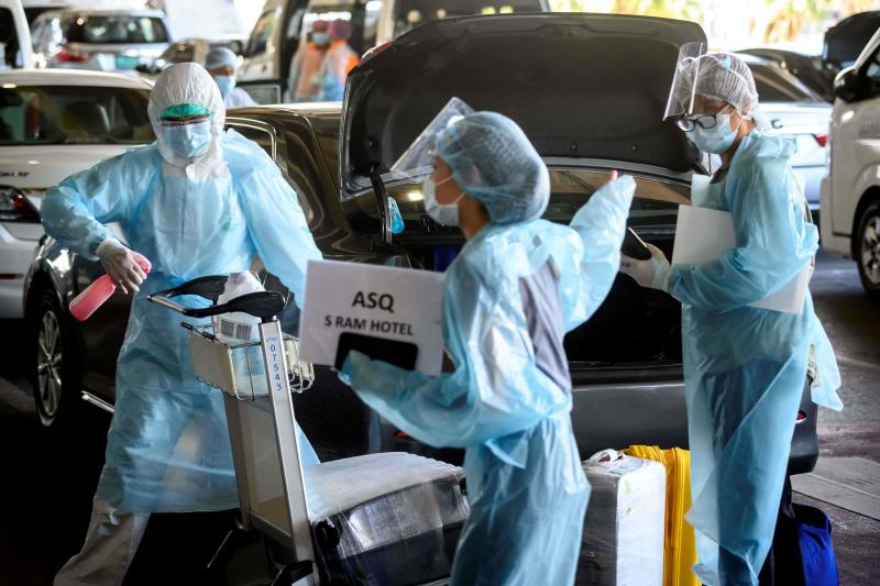 FILE PHOTO: An employee (left) wearing personal protective equipment (PPE) disinfects the luggage of arriving international flight passengers before their transfer to a hotel for the compulsory 14-day Alternative State Quarantine (ASQ), to prevent the spread of the Covid-19 coronavirus, at Suvarnabhumi Airport in Samut Prakan province on Nov 16, 2020. (AFP)