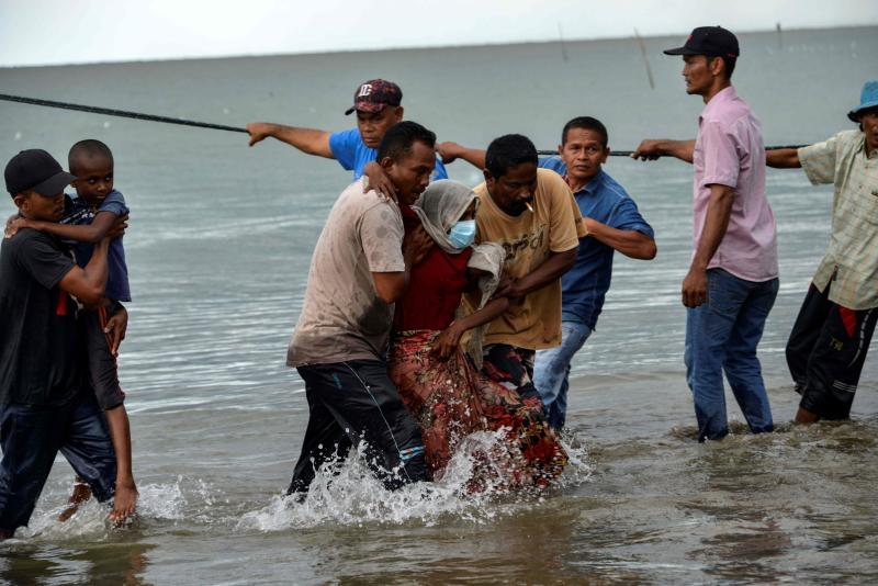 FILE PHOTO: Acehnesse fishermen help evacuate a Rohingya child and a woman from Myanmar onto the shorelines of Lancok village in Indonesia's North Aceh Regency on June 25, 2020. (AFP)