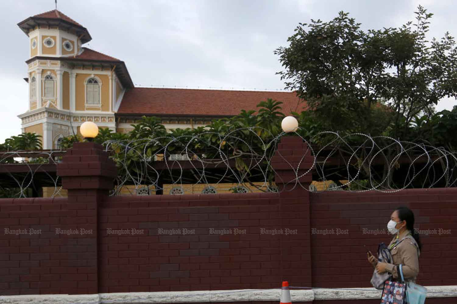 Razor wire is installed on the walls of the Crown Property Bureau on Phitsanulok Road as part of stepped-up security  ahead of a planned protest by pro-democracy demonstrators on Wednesday. (Photo by Arnun Chonmahatrakool)