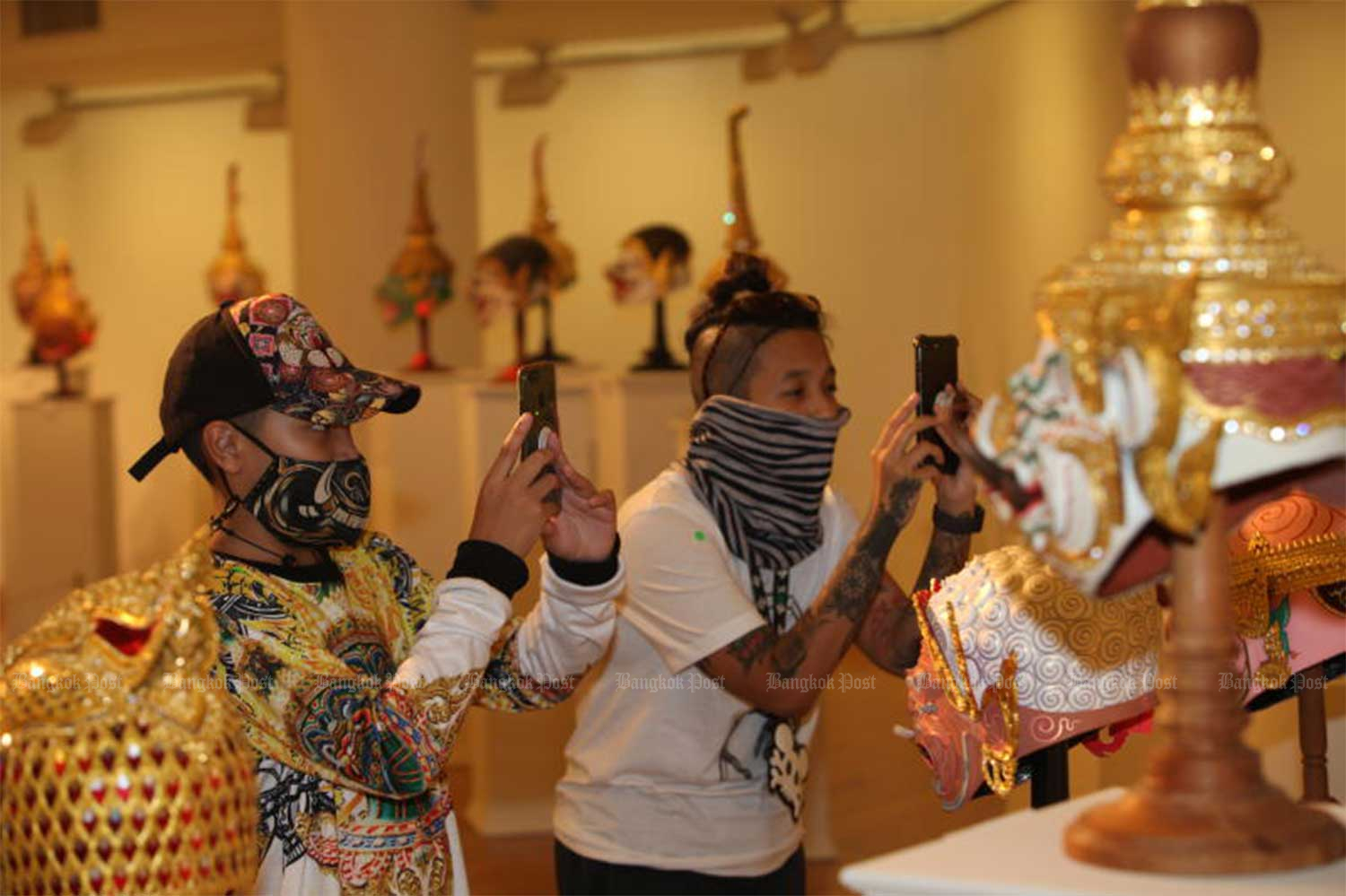 Visitors take photos of classical khon masks at an exhibition at the Queen's Gallery on Ratchadamnoen Klang Road in Bangkok's Phra Nakhon district on Nov 23. The  exhibition continues until Dec 22. (Photo: Apichart Jinakul)