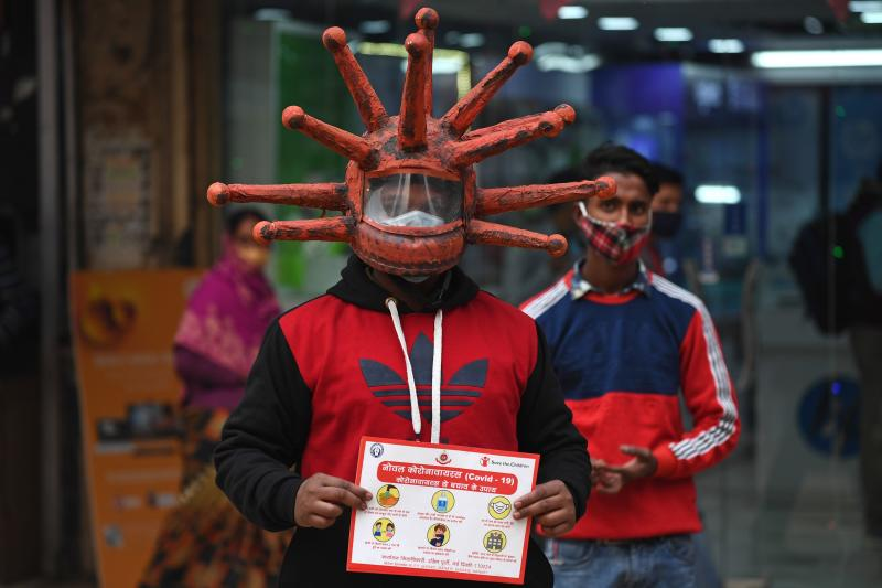 A civil defence volunteer wearing a Covid-19 coronavirus-themed helmet holds a placard as he takes part in an awareness campaign at a market in New Delhi on Wednesday. (AFP photo)