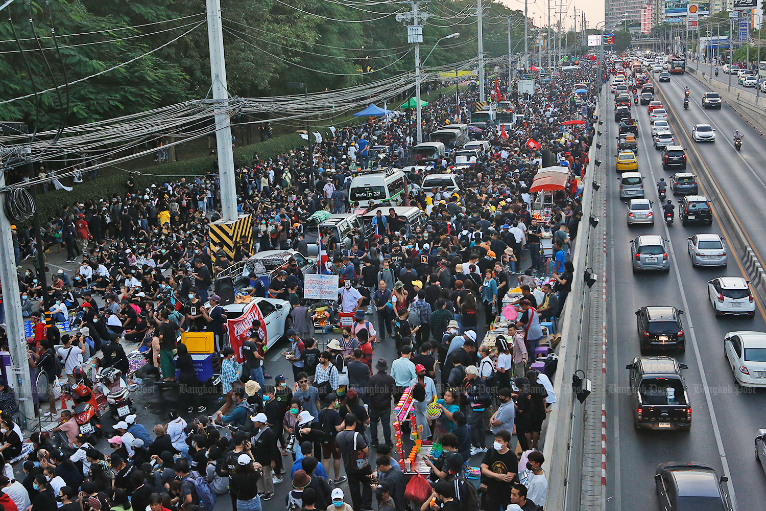 Anti-government protesters occupy the road outside the head office of Siam Commercial Bank near Ratchayothin intersection.(Photo by Arnun Chonmahatrakool)